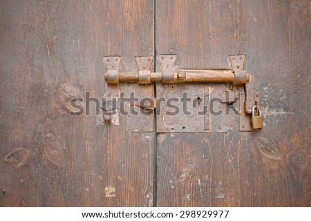 Ancient medieval gate blocked by a bolt and padlock - stock photo