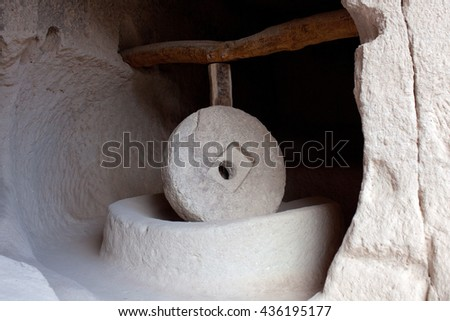 Ancient millstone in Zelve Open Air Museum in Cappadocia, Turkey. This process is being made by means of a stone 500 kg weight and 1,5 m. diameter moving by a rotation mechanism. - stock photo