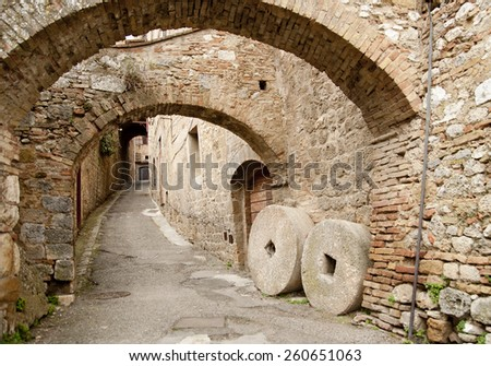 Ancient millstones in a narrow alley in San Gimignano, Tuscany - stock photo