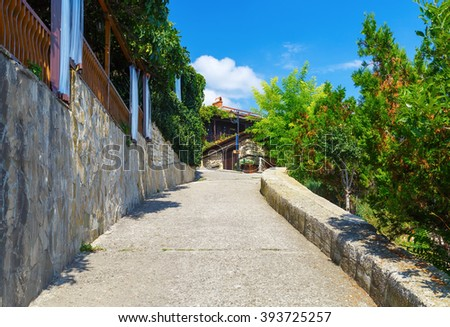 Ancient narrow street in the historic tourist town. Sidewalk in the old town of Nessebar in Bulgaria. - stock photo