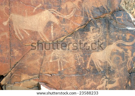 Ancient petroglyphic image of hunting for a buffalo. Area Tamgaly. - stock photo