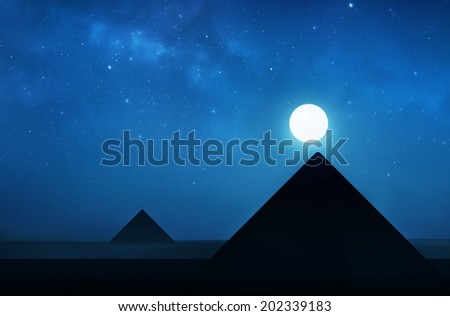 Ancient pyramids at night - night sky filled with stars - stock photo
