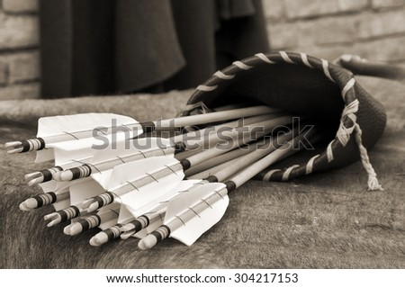 ancient quiver with arrows over the table - stock photo