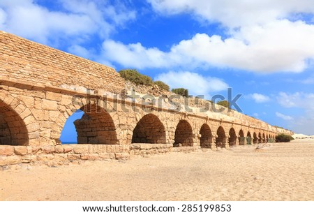 Ancient Roman aqueduct in Ceasarea at the coast of the Mediterranean Sea, Israel - stock photo