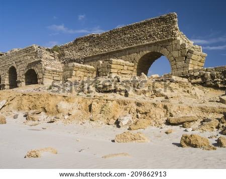 Ancient Roman aqueduct in Ceasaria, Israel - stock photo