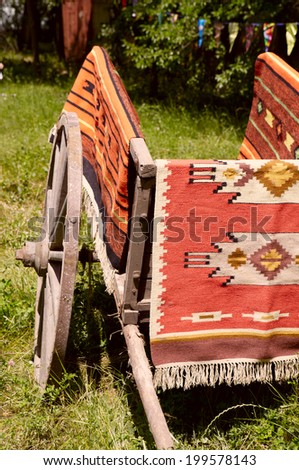 Ancient Romanian wooden cart standing on a green grass - stock photo