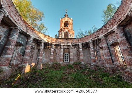 Ancient rotunda with columns without a dome on the bell tower of the background and blue sky at sunset. Abandoned brick temple overgrown with grass - stock photo