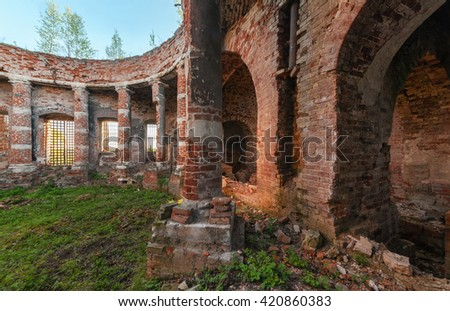 Ancient rotunda with columns without a dome. The brick ruins of the interior of an abandoned temple overgrown with grass - stock photo