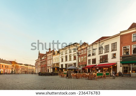 Ancient row of houses with restaurants and bars in the historic Dutch city of Zutphen during sunset - stock photo