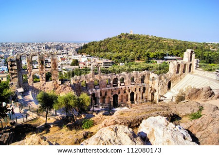 Ancient ruined Greek theatre at the Acropolis with Athens view behind - stock photo
