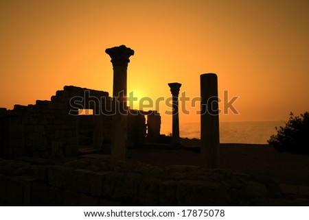 Ancient ruins during sunset with sea at background - stock photo