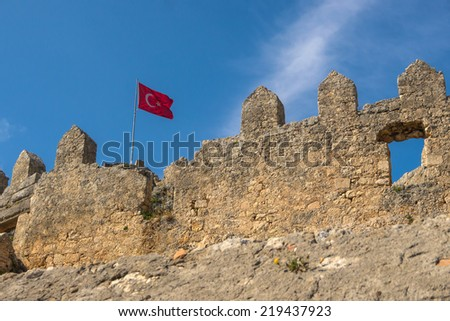 Ancient ruins of Byzantine fortress with Turkish flag in Burch bay near Simena village, Lycia, Turkey. DoF. - stock photo