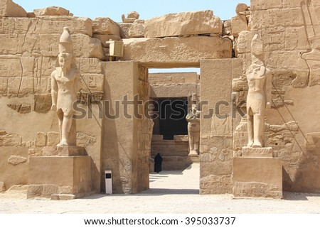 Ancient ruins of Karnak temple, statues of pharaohs on the pedestal, a woman in black goes to the temple. Luxor, Thebes, Egypt - stock photo