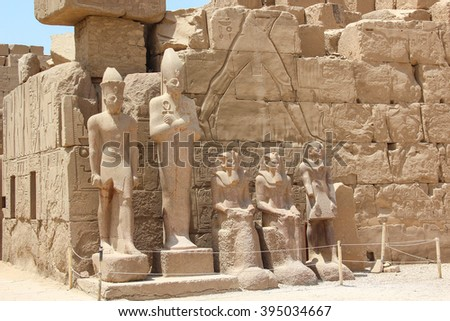 Ancient ruins of Karnak temple, statues of pharaohs, wifes and gods on the pedestal, Luxor, Thebes, Egypt - stock photo