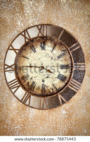 Ancient scratched vintage clock with roman numbers on the grunge wall background - stock photo