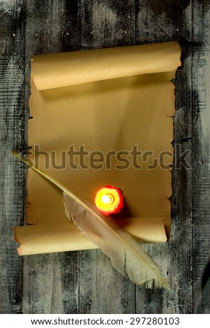 Ancient scroll rolled in wooden Background with Quill Pen and Candle top View - stock photo