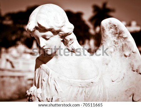 Ancient statue of a beautiful female angel with an out of focus background in sepia tones - stock photo