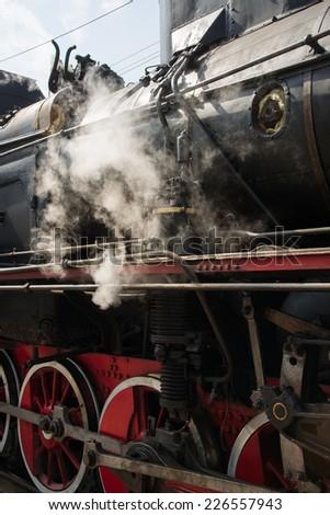 Ancient steam locomotive in steam. Live steam around mechanical parts, wheels and equipment of the train. The foretaste of an interesting travel. Vertical, portrait orientation photography - stock photo