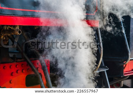 Ancient steam locomotive in steam. Live steam around mechanical parts, wheels and equipment of the train. The foretaste of an interesting travel. - stock photo