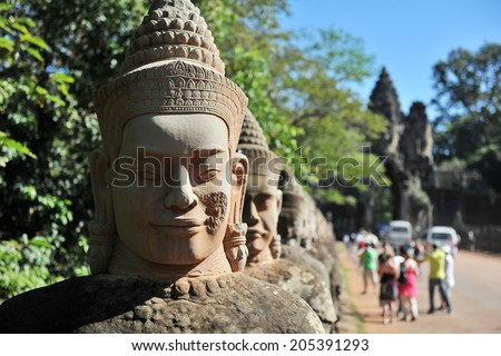 Ancient Stone Carved Statue Heads at the Entrance of the Historic Angkor Wat Temple Complex in Cambodia - stock photo