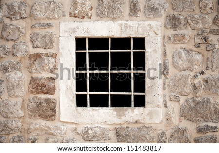 Ancient stone prison wall with metal window bars - stock photo