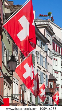 Ancient street Augustinergasse in Zurich decorated with swiss flags - stock photo