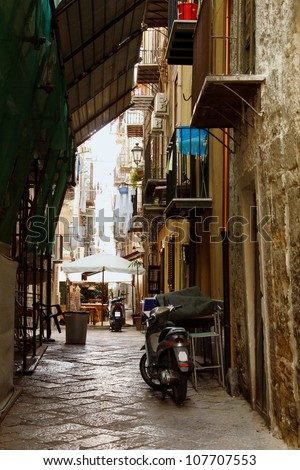 ancient street in Palermo with cobblestone road, Sicily, Italy - stock photo