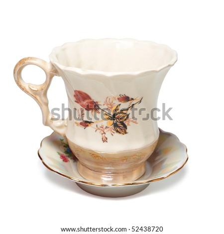 ancient teacup on saucer decorated with gold and roses - stock photo