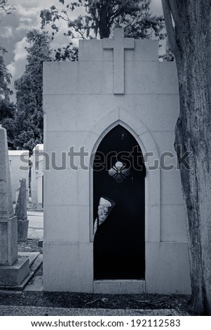 Ancient tomb of an old European cemetery. Black and white infrared toned blue. - stock photo