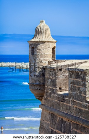 Ancient watchtower with the blue ocean and sky in the background - stock photo