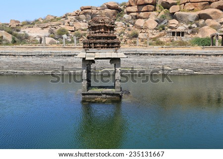 Ancient water pool and temple at Krishna market, Hampi, Karnataka state, India - stock photo