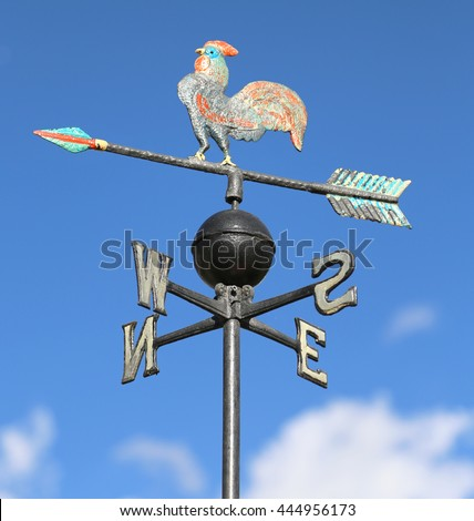 ancient weathervane with cock above an arrow and the four cardinal points North East West South - stock photo