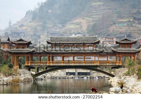 Ancient Wind-rain bridge in Xijiang Hmong village - stock photo