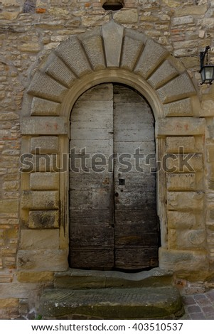 Ancient wooden door in a village of the Tuscan countryside - stock photo