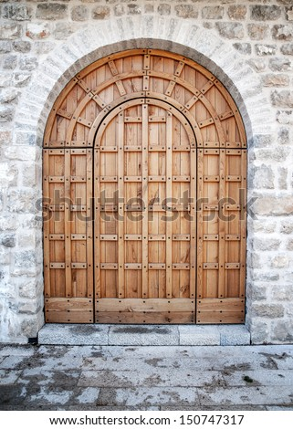Ancient wooden door in old stone castle wall.  - stock photo