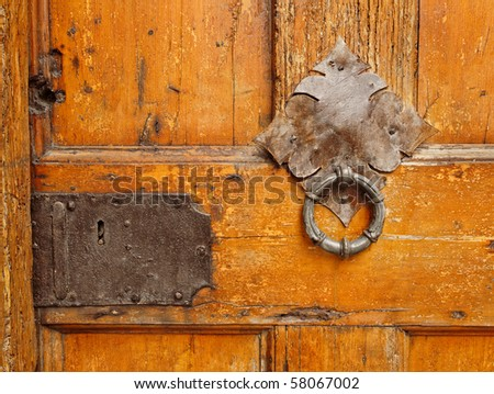 Ancient wooden  door with decorative door knocker - stock photo