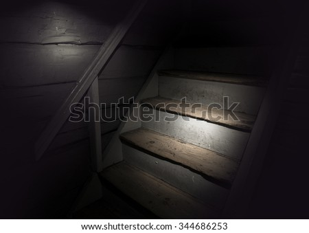 Ancient wooden staircase in dark building with spotlight - stock photo