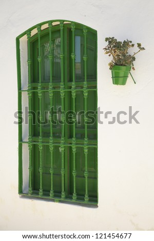 Andalusia. Geranium flower pot hanging from a traditional white wall in Andalusia, Spain. - stock photo