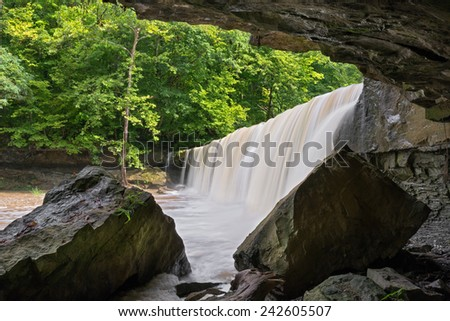 Anderson Falls, a wide waterfall near Columbus, Indiana, has a cave-like rock overhang at one end. - stock photo