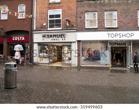 Andover, High Street, Hampshire, England - September 21, 2015: Topshop and Topman fashion store, H Samuel Jewellers and Costa Coffee, late rain soaked afternoon - stock photo