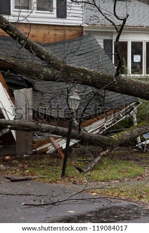 ANDOVER, NJ - OCT 30: A lamppost still standing in front of a tree laying across the front porch of a home after Hurricane Sandy made landfall in the US in Andover, New Jersey on October 30, 2012. - stock photo