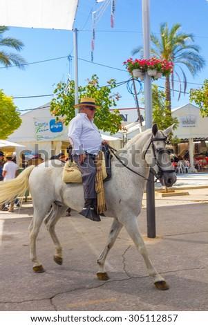 ANDUJAR,SPAIN - September, 6: mature men are walking in their mounts for the horse fairon September, 6, 2014 in Andujar, Spain - stock photo
