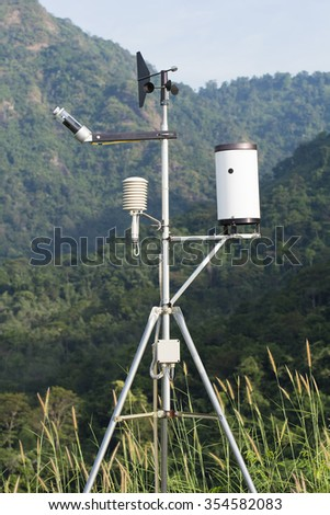 Anemometer and weather with a backdrop of green mountains and forest./  Anemometer and weather  - stock photo