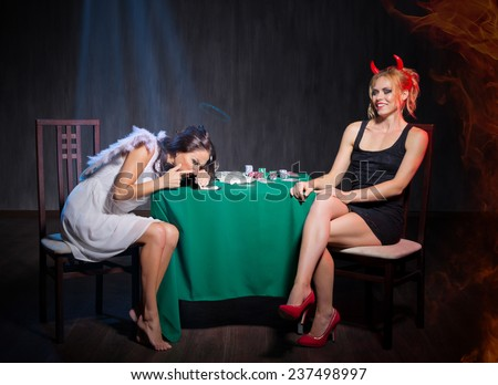 Angel and devil with drugs in dark room - stock photo