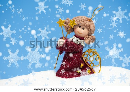 angel doll on snowdrift with snowflakes - stock photo