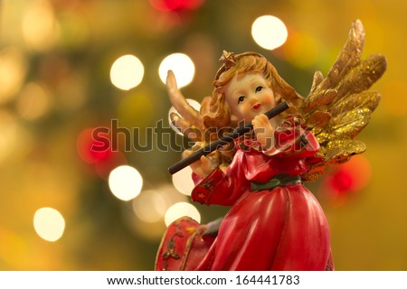 Angel figurine with flute over bokeh background on Christmas - stock photo