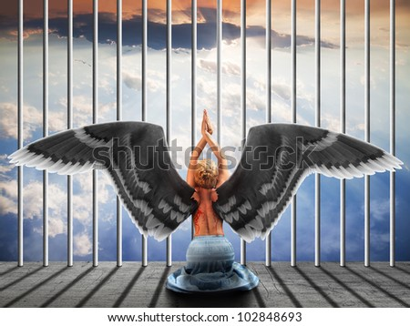 Angel, kneeling with his back. - stock photo