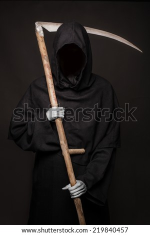 Angel of death with a scythe in his hands on black background. Halloween. Studio portrait on black background    - stock photo