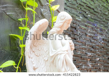 Angel statue in garden. - stock photo