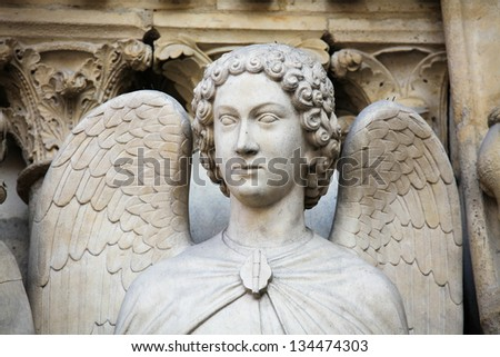 Angel statue in the Portal of the Virgin at Notre Dame Cathedral in Paris, France. - stock photo